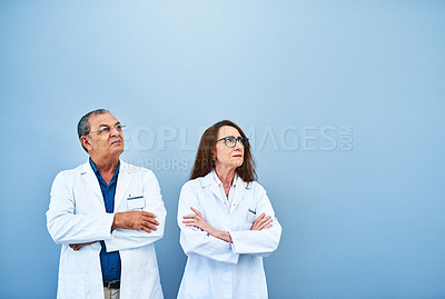 Buy stock photo Studio shot of two scientists looking up against a blue background
