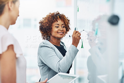 Buy stock photo Shot of two businesswomen brainstorming notes on a whiteboard in an office