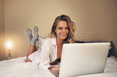 Buy stock photo Shot of a relaxed young woman using a laptop in her bedroom at home