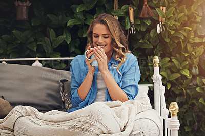 Buy stock photo Shot of a young woman having coffee and relaxing in the garden at home