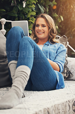 Buy stock photo Shot of a young woman using a digital tablet while relaxing in the garden at home