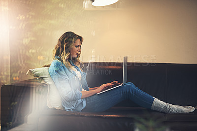 Buy stock photo Shot of a relaxed young woman using a laptop on the sofa at home