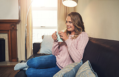 Buy stock photo Shot of a relaxed young woman having coffee on the sofa at home