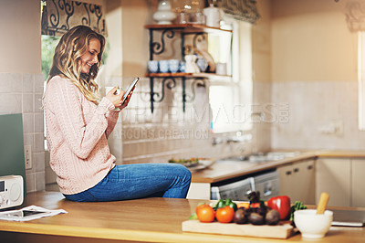 Buy stock photo Shot of a relaxed young woman having coffee and using a digital tablet at home