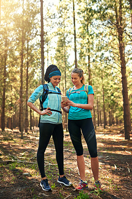 Buy stock photo Shot of two sporty young woman using a cellphone while out in nature