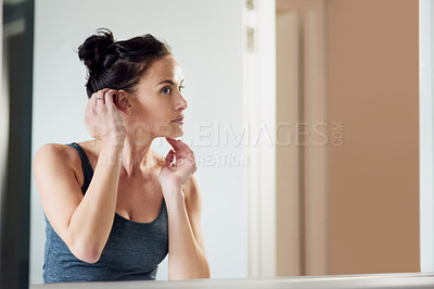 Buy stock photo Cropped shot of an attractive woman admiring her face in the bathroom mirror