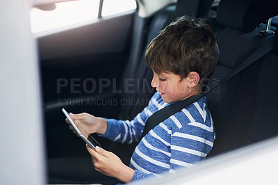 Buy stock photo Cropped shot of an adorable little boy using a digital tablet in the backseat of a car