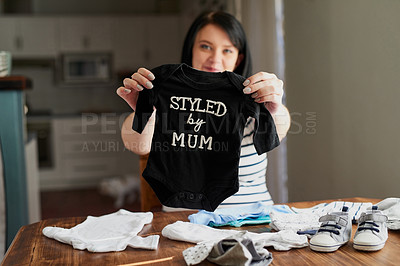 Buy stock photo Shot of a young pregnant woman sorting baby clothes at home