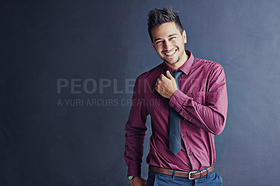 Buy stock photo Studio portrait of a smiling young businessman standing against a gray background