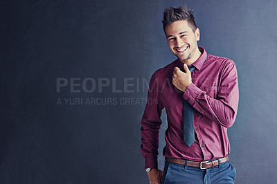 Buy stock photo Cropped studio portrait of a smiling young businessman standing against a gray background