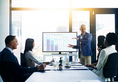 Buy stock photo Shot of a businessman delivering a presentation to his colleagues in the boardroom