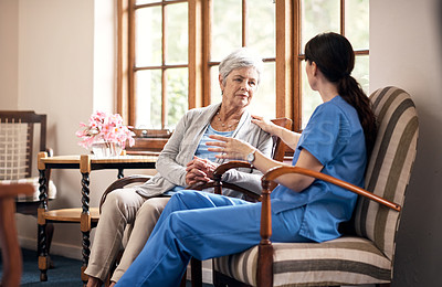 Buy stock photo Shot of a young nurse talking with an elderly woman in a retirement home