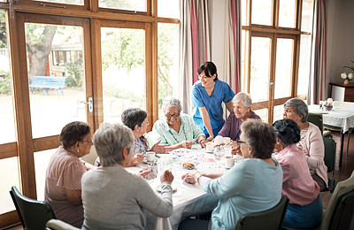 Buy stock photo Shot of a group of senior women playing cards together at a retirement home