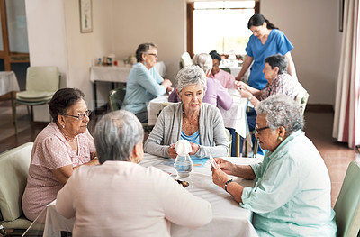 Buy stock photo Shot of a group of senior women playing cards together at a retirement home during the day