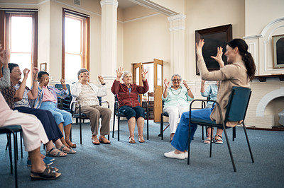 Buy stock photo Full length shot of a female fitness instructor taking a class in an old age home