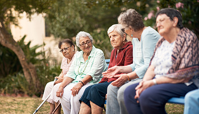 Buy stock photo Cropped shot of a group of seniors sitting on a bench outside