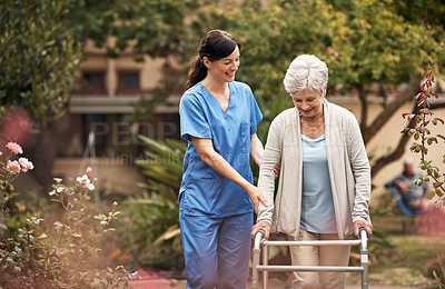Buy stock photo Shot of a senior woman with her walker out for a stroll in the garden with her caregiver