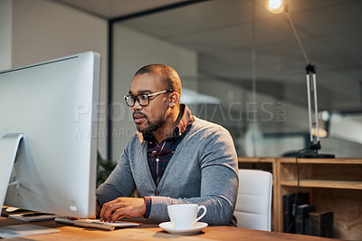 Buy stock photo Shot of a focused young businessman working in his office