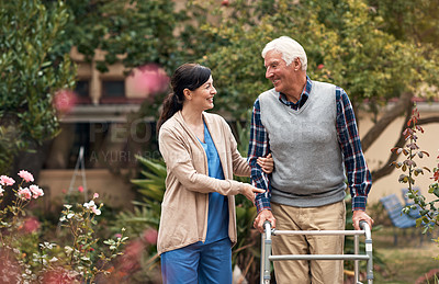 Buy stock photo Shot of a senior man with his walker out for a stroll in the garden with his caregiver