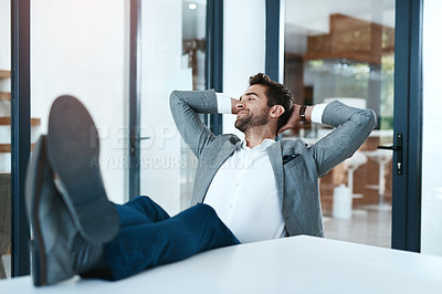 Buy stock photo Shot of a handsome young businessman relaxing with his feet up on a desk in a modern office
