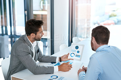 Buy stock photo Cropped shot of two young businessmen going through paperwork together in a modern office