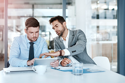 Buy stock photo Cropped shot of two young businessmen using a digital tablet while going through paperwork together in a modern office