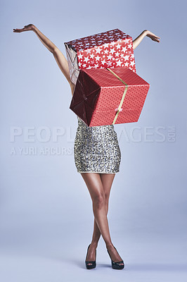 Buy stock photo Studio shot of a young woman throwing gifts while standing against a blue background