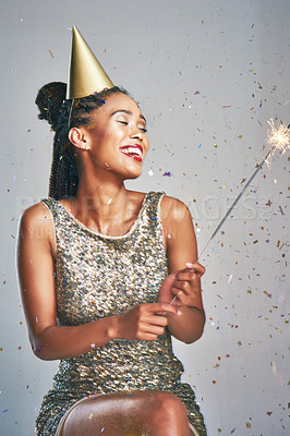 Buy stock photo Shot of a young woman wearing a party hat while holding a sparkler