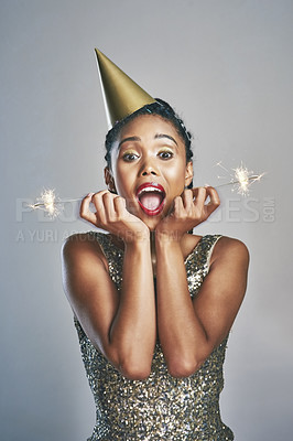 Buy stock photo Shot of a young woman wearing a party hat while holding sparklers