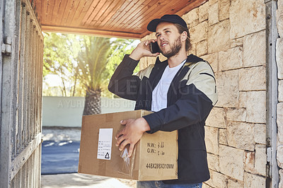 Buy stock photo Cropped shot of a courier talking on his cellphone while out on delivery