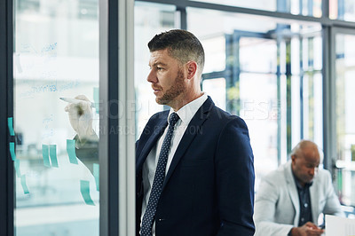 Buy stock photo Shot of a mature businessman writing notes on a glass wall with his colleague in the background in an office