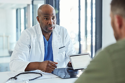 Buy stock photo Shot of a doctor using a digital tablet while having a consultation with a patient in his office