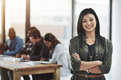 Buy stock photo Portrait of a cheerful businesswoman posing with her arms folded in a modern office with her colleagues in the background