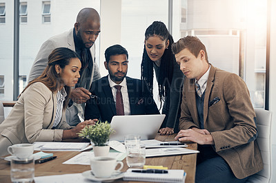 Buy stock photo Shot of a group of young businesspeople using a laptop together during a meeting in a modern office