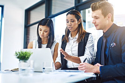 Buy stock photo Cropped shot of a group of young businesspeople having a discussion while using a laptop in a modern office