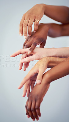 Buy stock photo Cropped studio shot of a group of women touching hands against a gray background