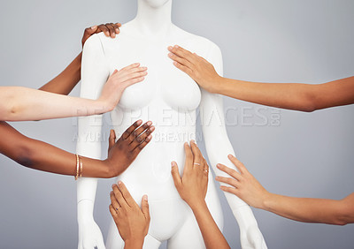 Buy stock photo Cropped studio shot of a group of women touching a mannequin against a gray background