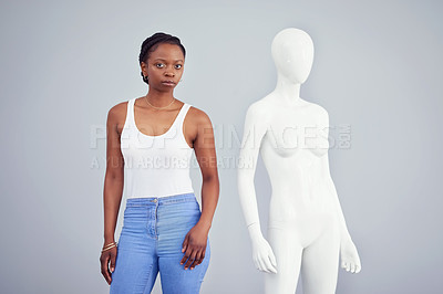 Buy stock photo Studio shot of a young woman posing next to a mannequin against a grey background