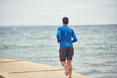 Buy stock photo Rearview shot of a sporty man out running by the seaside