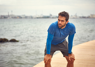 Buy stock photo Shot of a sporty man taking a break after his run