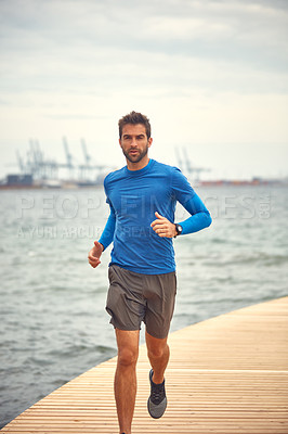 Buy stock photo Shot of a sporty middle-aged man out running by the seaside