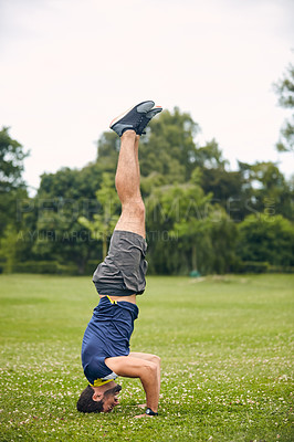 Buy stock photo Shot of a sporty middle-aged man doing a headstand