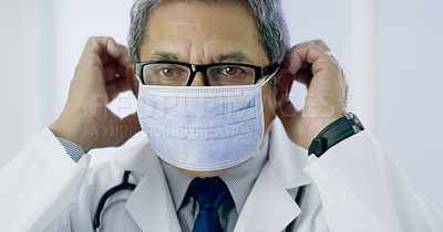 Buy stock photo Cropped portrait of a handsome mature male doctor preparing for surgery in the hospital