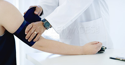 Buy stock photo Cropped shot of an unrecognizable male doctor taking a female patient's blood pressure in the hospital