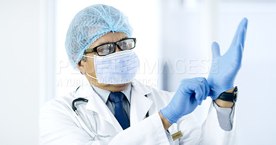 Buy stock photo Cropped shot of a handsome mature male doctor preparing for surgery in the hospital