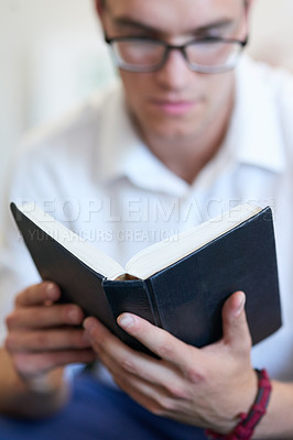 Buy stock photo Shot of a handsome young businessman reading his bible at work