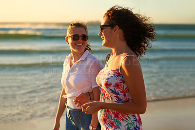 Buy stock photo Cropped shot of two attractive young girlfriends having a chat while strolling on the beach