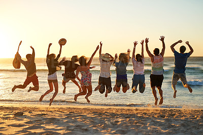 Buy stock photo Rearview shot of a group of young friends jumping into the air at the beach