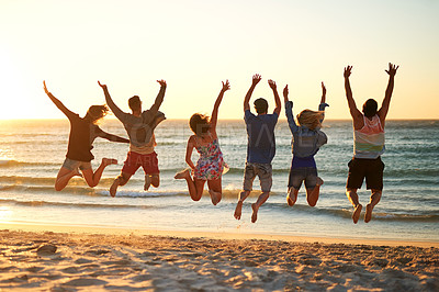 Buy stock photo Rearview shot of a group of friends jumping into mid air at the beach