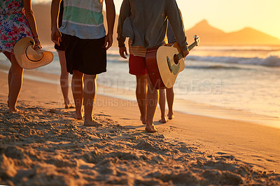 Buy stock photo Rearview shot of a group of unrecognizable friends walking together on the beach